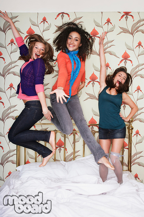 Teenage Girls arms outspread jumping on bed