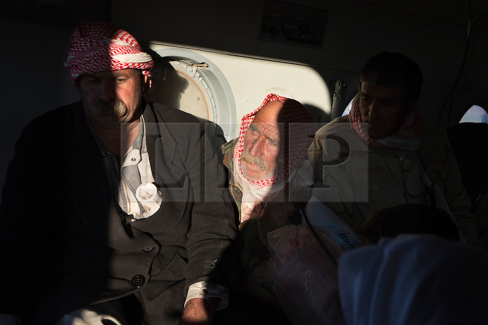 © Licensed to London News Pictures. 11/12/2014. Fishkhabour, Iraq. An elderly Yazidi refugee is illuminated by sunlight streaming in through the window of an Iraqi Air Force Mi-17 Hip helicopter as he and others are evacuated from Mount Sinjar.<br /> <br /> Although a well publicised exodus of Yazidi refugees took place from Mount Sinjar in August 2014 many still remain on top of the 75 km long ridge-line, with estimates varying from 2000-8000 people, after a corridor kept open by Syrian-Kurdish YPG fighters collapsed during an Islamic State offensive. The mountain is now surrounded on all sides with winter closing in, the only chance of escape or supply being by Iraqi Air Force helicopters. Photo credit: Matt Cetti-Roberts/LNP