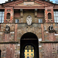 """Porta San Pietro Wall Entrance in Lucca, Italy<br /> A huge, Renaissance wall surrounds Lucca, Italy, and this is one of several entrances.  Called Porta San Pietro, it was built on the south side of town in the mid-16th century by Alessandro Resta.  Above the arch is an emblem of St. Peter flanked by two lion statues.  In the pediment is the word """"Libertas.""""  It promises a delightful, historic visit ahead that dates back to an ancient Roman colony."""