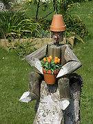 sitting wooden flowerpot figurine holding tulips in a pot
