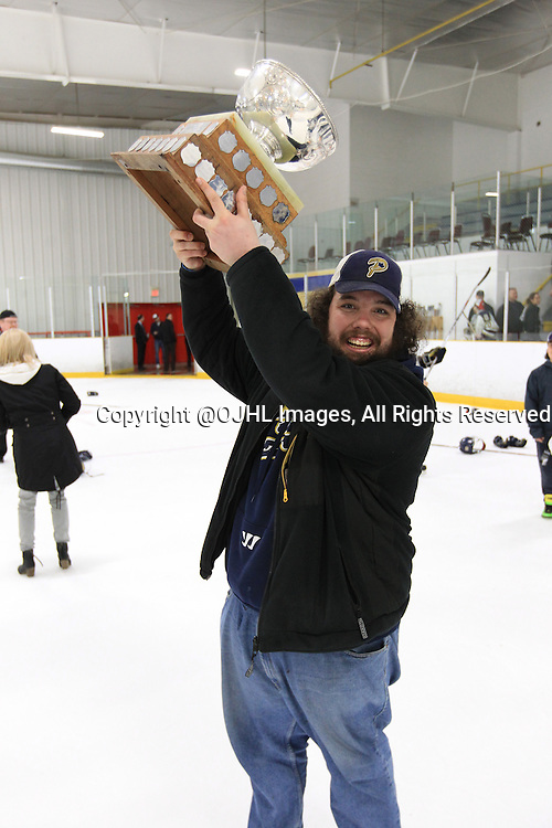 TORONTO, ON - Apr 22, 2015 : Ontario Junior Hockey League game action between the Toronto Patriots and the Kingston Voyageurs. Game seven of the Buckland Cup Championship Series. Patriots time keeper poses with the Cup.<br /> (Photo by Tim Bates / OJHL Images)