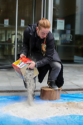 © Licensed to London News Pictures. 15/11/2019. London, UK. An activist from Extinction Rebellion climate change group dumps pile of wood ash (waste collected from pizza ovens and wood burning stoves) outside the offices of asset manager BlackRock in City of London. BlackRock is the world's top investor in deforestation and coal, the top US investor in oil & gas, and one of the world's largest asset managers, controlling more funds than the GDP of Japan.Photo credit: Dinendra Haria/LNP