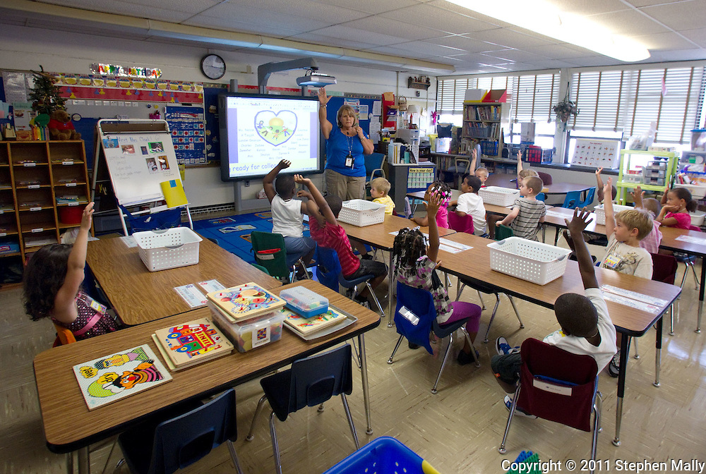 Karen Clark, of Cedar Rapids, leads her kindergarten class on the first day of school at Polk Elementary School, 1500 B Avenue NE, in Cedar Rapids on Thursday morning, July 21, 2011.