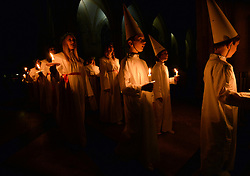 © Licensed to London News Pictures. 11/12/2015. York, UK. Members of the Vaxholm boys' choir with the Chorus Pictor choir from Stockholm during the Sankta Lucia Carol Service at York Minster. Lucia is a tradition in the Swedish calendar and is a celebration of St Lucy as the bringer of light in the darkness of winter.  Photo credit : Anna Gowthorpe/LNP
