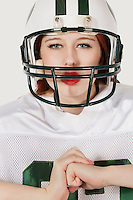 Portrait of young woman in football uniform against gray background