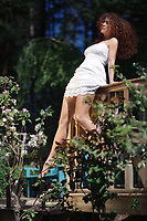 Young woman in a white summer dress sitting on the edge of balcony railings in a garden enjoying sunshine in spring