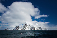 Mountainous island with dark blue ocean, sky and clouds, Gerlache Strait, Antarctica. Landscape and nature photography wall art. Fine art photography prints.