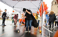"Gregory DeLuca watches as Anthony DeLuca and Conner Jay play ""Pumpkin Sweep"" at the Berkshire Hathoway tent during Pumpkin Fest on Saturday afternoon.  (Karen Bobotas/for the Laconia Daily Sun)"