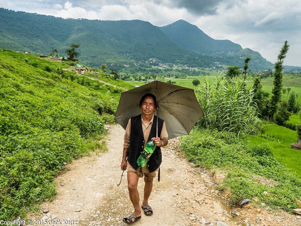04 AUGUST 2015 - KHOKANA, NEPAL:  A farmer walks up a dirt road in Khokana, Nepal. He had been working in his rice fields.       PHOTO BY JACK KURTZ