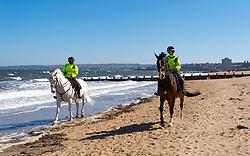 Portobello, Scotland, UK. 19 April 2020. Police horses patrol the promenade and beach at Portobello on sunny Sunday afternoon. Iain Masterton/Alamy Live News