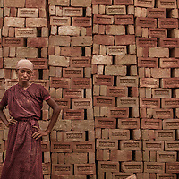 A female brickfield worker standing in front of stake of bricks in Ashulia, savar.<br /> <br /> With recent boom in construction industry small-scale production of bricks has emerged as an important manufacturing activity with the brickfields providing seasonal employment to thousands of migrant workers