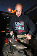 Farrier preparing a horseshoe in his mobile workshop Shaping the heated shoe