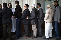 © Licensed to London News Pictures . 12/05/2017 . Manchester , UK . People queue by the coffin to hug family as they arrive for the service . Thousands of people fill a mosque , inside a marquee at the British Muslim Heritage Centre in Whalley Range , Manchester , for the funeral of Mawlana Habib-ur-Rahman , at the British Muslim Heritage Centre , Whalley Range , Manchester . Rahman , a former maths teacher and then imam at Manchester Central Mosque , died aged 90 following heart problems . As a well-known leader of Manchester's Muslim community he promoted interfaith dialogue and met the Pope during a Papal visit to Manchester in 1982 . Due to the number attending , crowds attending the funeral had to be diverted to rooms in nearby buildings to listen to the service via loudspeaker . Photo credit : Joel Goodman/LNP