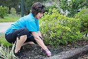 Rachel Lambert pulls weeds near the Town parking lot during the Trash Bash sponsored by Keep Abita Beautiful in Abita Springs, Louisiana