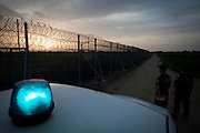 Police officers stand guard at the 12.5-kilometer barbed-wire fence along the land border with Turkey, which was met with skepticism at home as well as from many EU officials. It has allegedly succeeded in blocking one of the most popular transit routes for migrants seeking to make their way to the west