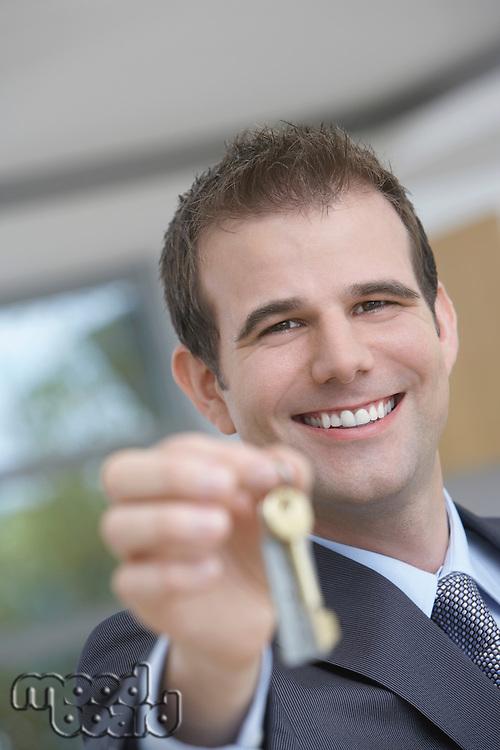 Real estate agent holding key indoors portrait