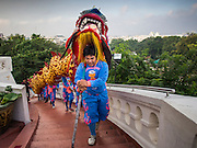 30 OCTOBER 2014 - BANGKOK, THAILAND: A dragon dance troupe climbs the 316 steps up the Wat Saket chedi hill during the parade marking the start of the annual temple fair at Wat Saket. Wat Saket is on a man-made hill in the historic section of Bangkok. The temple has golden spire that is 260 feet high which was the highest point in Bangkok for more than 100 years. The temple construction began in the 1800s in the reign of King Rama III and was completed in the reign of King Rama IV. The annual temple fair is held on the 12th lunar month, for nine days around the November full moon. During the fair a red cloth (reminiscent of a monk's robe) is placed around the Golden Mount while the temple grounds hosts Thai traditional theatre, food stalls and traditional shows.   PHOTO BY JACK KURTZ