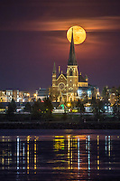 A full yellow moon rises behind the spire of one of the defining features of Portland's skyline, the Cathedral of the Immaculate Conception on Congress Ave.