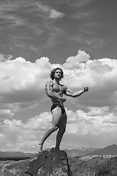 hot male bodybuilder posing outdoors on a rock