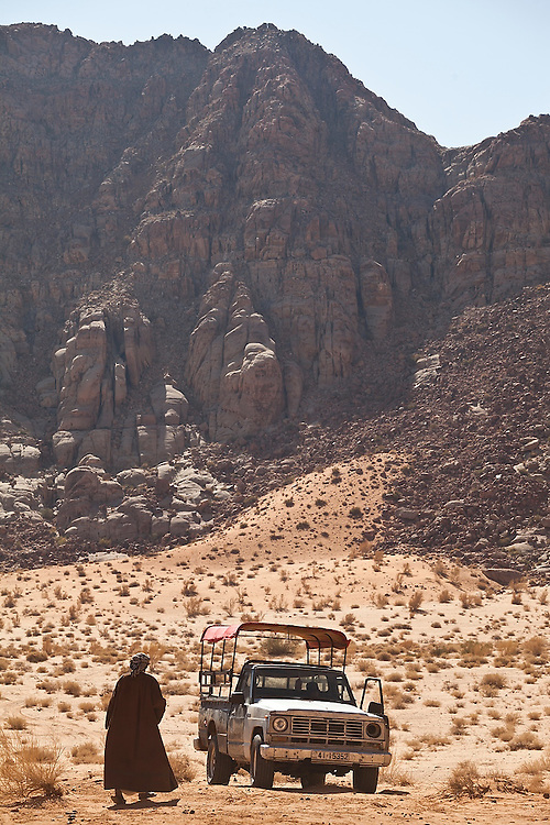 Bedouin guide Etzal Salem walks to his pickup truck in the desert in Wadi Rum, Jordan.