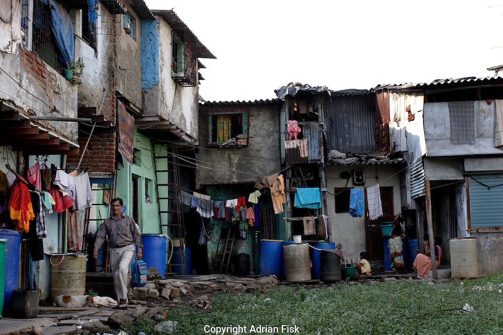By a clearing a man walks past Dharavi slum houses on 21st Oct 2006.
