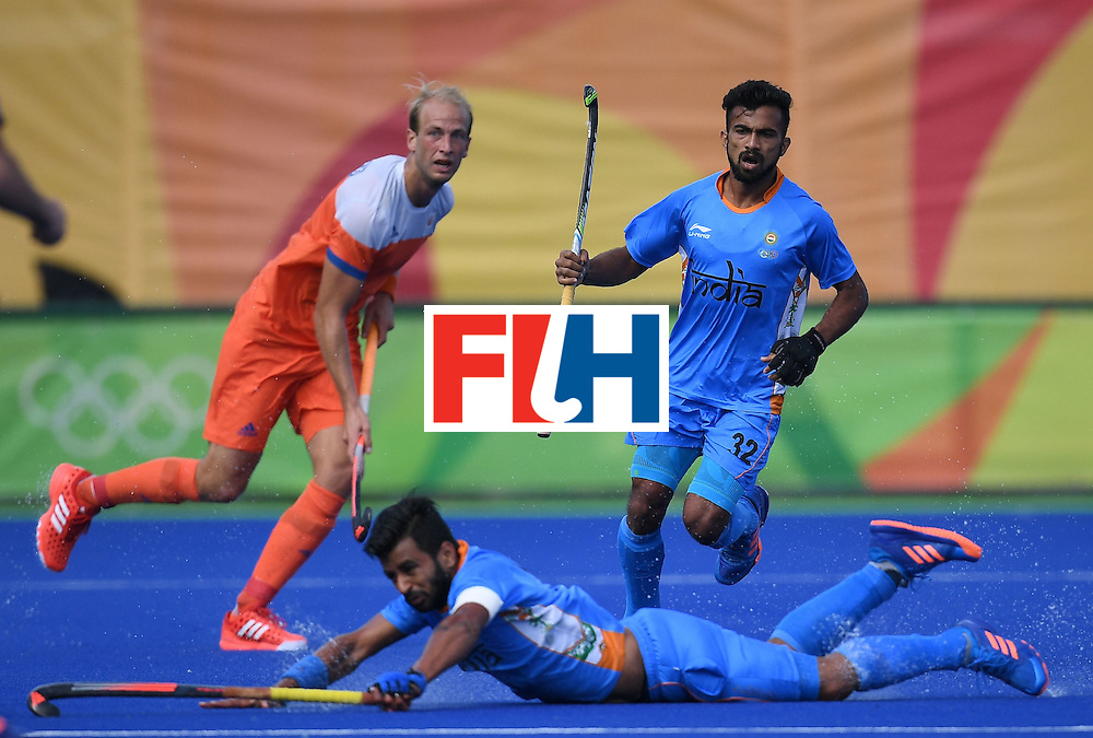 Netherland's Billy Bakker (L) and India's Chandanda Thimmaiah look on as India's Manpreet Singh dives for the ball during the men's field hockey Netherland's vs India match of the Rio 2016 Olympics Games at the Olympic Hockey Centre in Rio de Janeiro on August, 11 2016. / AFP / MANAN VATSYAYANA        (Photo credit should read MANAN VATSYAYANA/AFP/Getty Images)