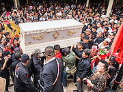 28 APRIL 2014 - BANGKOK, THAILAND: The coffin bearing Kamol Duangphasuk, 45, is brought through the crowd at Wat Samian Nari during his funeral in Bangkok. Kamol was a popular poet who wrote under the pen name Mai Nueng Kor Kunthee. Kamol had been writing since the 1980s and was an outspoken critic of the 2006 coup that deposed Thaksin Shinawatra. After the 2010 military crackdown against the Red Shirts he went into temporary self imposed exile fearing for his safety. After he returned to Thailand he organized weekly protests against Thailand's Lese Majeste laws, which he said were being used to stifle dissent. Kamol was shot and murdered on April 23. The assailants are still at large but the murder is thought to be political.     PHOTO BY JACK KURTZ
