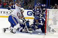 Tampa Bay Lightning defenseman Sami Salo (6) jumps on a loose puck in front of goalie Anders Lindback and Montreal Canadiens' Brandon Prust during the first period of an NHL hockey game in Tampa, Florida February 12, 2013.  REUTERS/Mike Carlson (UNITED STATES)