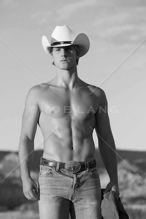 shirtless cowboy outdoors at sunset