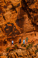Tourists hike to see large lizard petroglyphs at Cub Creek in Dinosaur National Monument, Utah USA. The large lizard figures found here are not common at other sites.