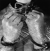 Hands in Bondage Leather and Plastic Wrap