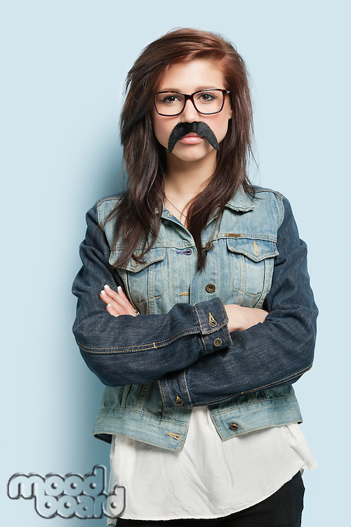 Portrait of young woman wearing fake mustache with arms crossed against light blue background