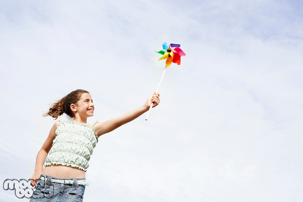 Smiling pre-teen Girl Holding Pinwheel above head low angle view