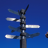 South Africa, Table Mountain National Park, Man's hand and international signpost at Cape of Good Hope against blue sky
