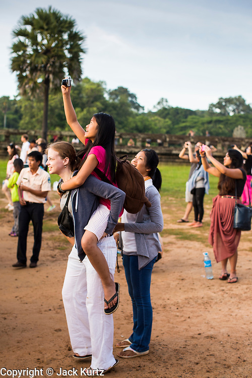 "02 JULY 2013 - ANGKOR WAT, SIEM REAP, SIEM REAP, CAMBODIA:  A tourist uses her smart phone to photograph the Angkor Wat sunrise. Angkor Wat is the largest temple complex in the world. The temple was built by the Khmer King Suryavarman II in the early 12th century in Yasodharapura (present-day Angkor), the capital of the Khmer Empire, as his state temple and eventual mausoleum. Angkor Wat was dedicated to Vishnu. It is the best-preserved temple at the site, and has remained a religious centre since its foundation – first Hindu, then Buddhist. The temple is at the top of the high classical style of Khmer architecture. It is a symbol of Cambodia, appearing on the national flag, and it is the country's prime attraction for visitors. The temple is admired for the architecture, the extensive bas-reliefs, and for the numerous devatas adorning its walls. The modern name, Angkor Wat, means ""Temple City"" or ""City of Temples"" in Khmer; Angkor, meaning ""city"" or ""capital city"", is a vernacular form of the word nokor, which comes from the Sanskrit word nagara. Wat is the Khmer word for ""temple grounds"", derived from the Pali word ""vatta."" Prior to this time the temple was known as Preah Pisnulok, after the posthumous title of its founder. It is also the name of complex of temples, which includes Bayon and Preah Khan, in the vicinity. It is by far the most visited tourist attraction in Cambodia. More than half of all tourists to Cambodia visit Angkor.         PHOTO BY JACK KURTZ"