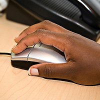 Close-up of an African-American's hand on a computer mouse