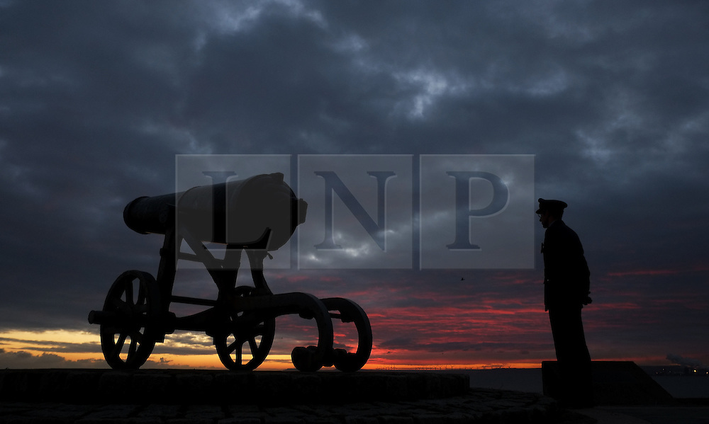 © Licensed to London News Pictures. <br /> 16/12/2014. <br /> <br /> Hartlepool, United Kingdom<br /> <br /> Flight Lieutenant Anthony Moy from Hartlepool Air Cadets stands next to a gun at sunrise during a memorial event to commemorate the bombardment of Hartlepool by German warships during World War One. During the bombardment 130 civilians were killed and more than 500 were wounded. The Headland's Heugh Gun Battery returned fire in what was the only battle to be fought on British soil during World War One, and one of the Battery's soldiers, Theo Jones of the Durham Light Infantry, became the first British soldier to be killed by enemy action on home ground in the war.<br /> <br /> Photo credit : Ian Forsyth/LNP