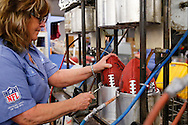 Doris Kast places an official game ball for the NFL football Super Bowl XLIX in a molding press for the final shaping at the Wilson Sporting Goods Co. in Ada, Ohio, Tuesday, Jan. 20, 2015. The New England Patriots will play the Seattle Seahawks in the Super Bowl on Feb. 1 in Glendale, Arizona. (AP Photo/Rick Osentoski)