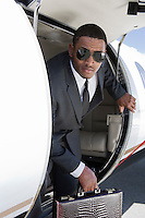 African-American businessman getting off airplane.