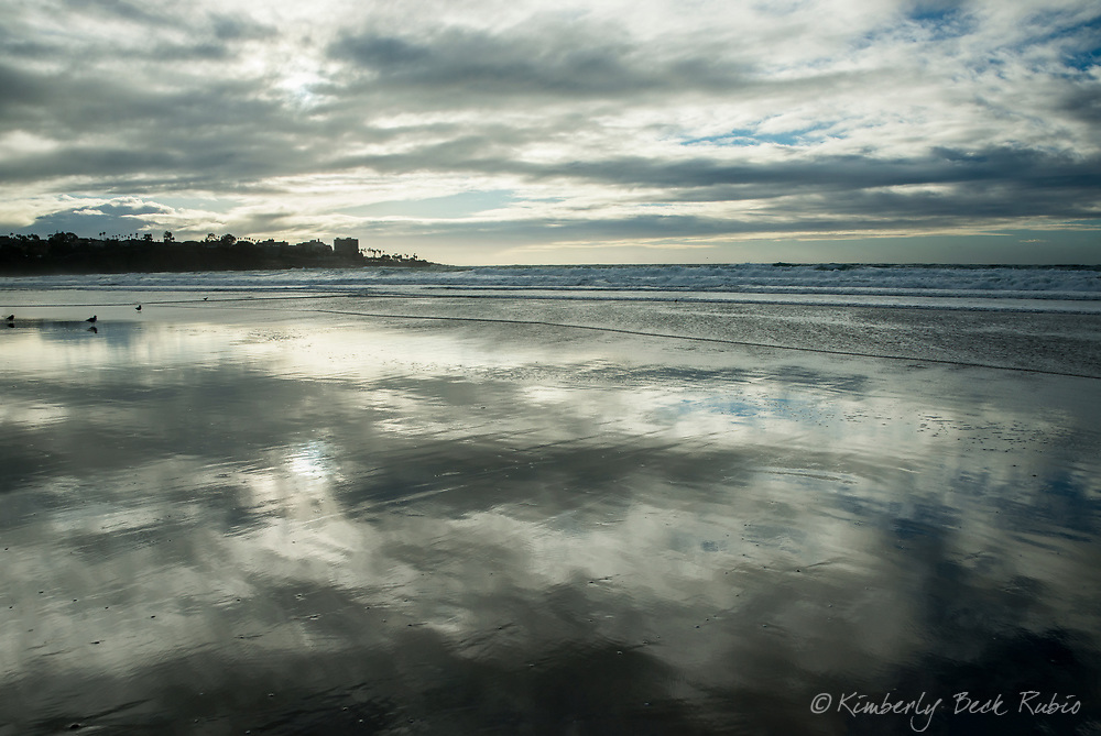 Sunset reflecting on the wet sand at La Jolla Shores beach on a rare stormy day in La Jolla, California.