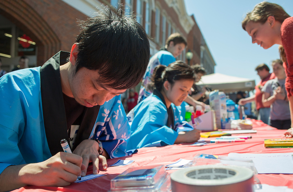 Yuto Arai, a sophomore international student from Japan, writes names in katakana, a Japanese writing style mostly used for words outside the Japanese language, at the International Street Fair on April 16, 2016.
