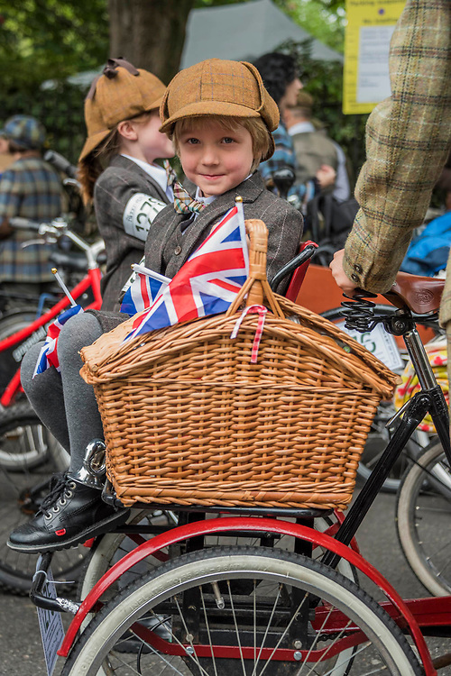 """A family dressed in home made suits (made by their father who is not a tailor) - The Tweed Run - a group bicycle ride through the centre of London, in which the cyclists are expected to dress in traditional British cycling attire, particularly tweed plus four suits. Any bicycle is acceptable on the Tweed Run, but classic vintage bicycles are encouraged in an effort to recreate the spirit of a bygone era. The ride dubs itself """"A Metropolitan Cycle Ride With a Bit of Style."""" London 06 May 2017"""