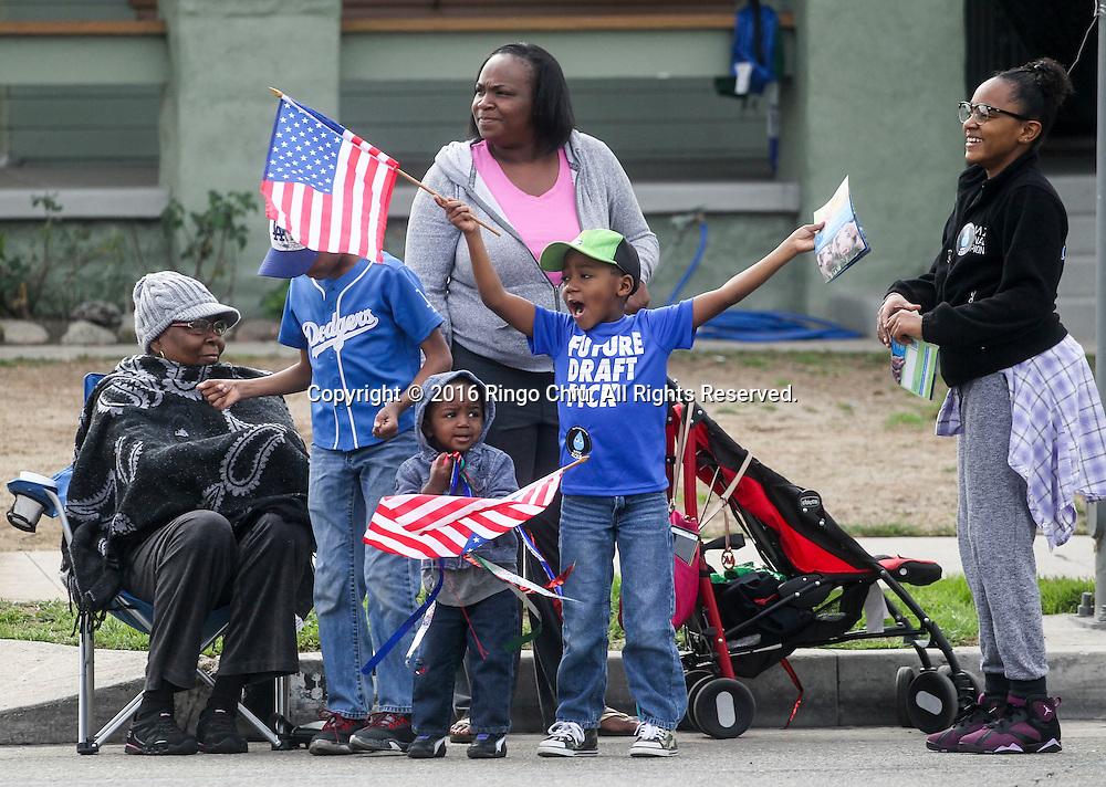 1月18日,在美国洛杉矶,观众向参加马丁&middot;路德&middot;金日纪念游行队伍挥旗。當天,洛杉矶举行了第31届马丁&middot;路德&middot;金日纪念游行。这是南加州最大的马丁&middot;路德&middot;金日纪念活动,今年的主题是&ldquo;我们的工作尚未完成&rdquo;。新华社发 (赵汉荣摄)<br /> Spectators watch in the 31st annual Kingdom Day Parade in Los Angeles, the United States, on Monday Jan. 18, 2016. The parade is Southern California's largest Martin Luther King Jr. Day observance. The theme of this year's parade was ``Our Work is Not Yet Done.''  (Xinhua/Zhao Hanrong)(Photo by Ringo Chiu/PHOTOFORMULA.com)<br /> <br /> Usage Notes: This content is intended for editorial use only. For other uses, additional clearances may be required.