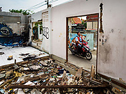 "22 MARCH 2018 - BANGKOK, THAILAND:  A motorcycle taxi goes past a demolished home along Khlong Lat Phrao. Bangkok officials are evicting about 1,000 families who have set up homes along Khlong  Lat Phrao in Bangkok, the city says they are ""encroaching"" on the khlong. Although some of the families have been living along the khlong (Thai for ""canal"") for generations, they don't have title to the property, and the city considers them squatters. The city says the residents are being evicted so the city can build new embankments to control flooding. Most of the residents have agreed to leave, but negotiations over compensation are continuing for residents who can't afford to move.     PHOTO BY JACK KURTZ"
