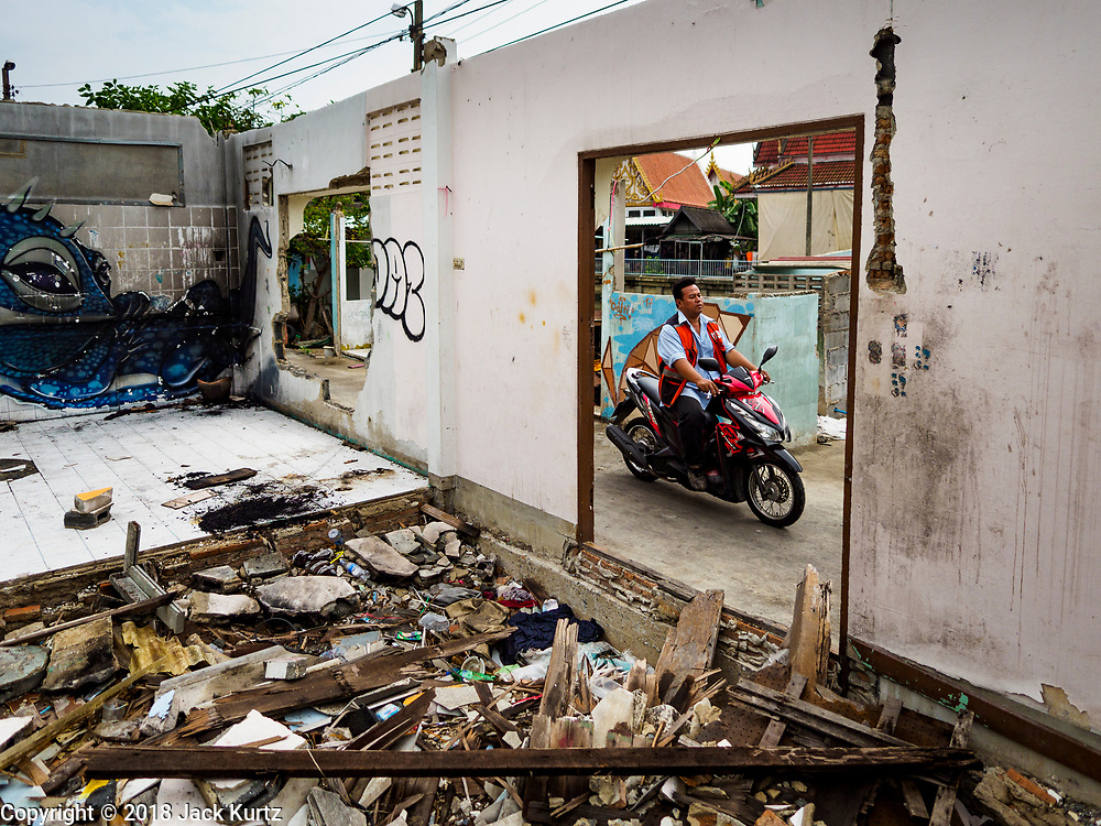 """22 MARCH 2018 - BANGKOK, THAILAND:  A motorcycle taxi goes past a demolished home along Khlong Lat Phrao. Bangkok officials are evicting about 1,000 families who have set up homes along Khlong  Lat Phrao in Bangkok, the city says they are """"encroaching"""" on the khlong. Although some of the families have been living along the khlong (Thai for """"canal"""") for generations, they don't have title to the property, and the city considers them squatters. The city says the residents are being evicted so the city can build new embankments to control flooding. Most of the residents have agreed to leave, but negotiations over compensation are continuing for residents who can't afford to move.     PHOTO BY JACK KURTZ"""