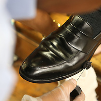 Pee Wee burshes on some leather sole & heel edge dressing on McCain's shoes to finish off the shoe shine.