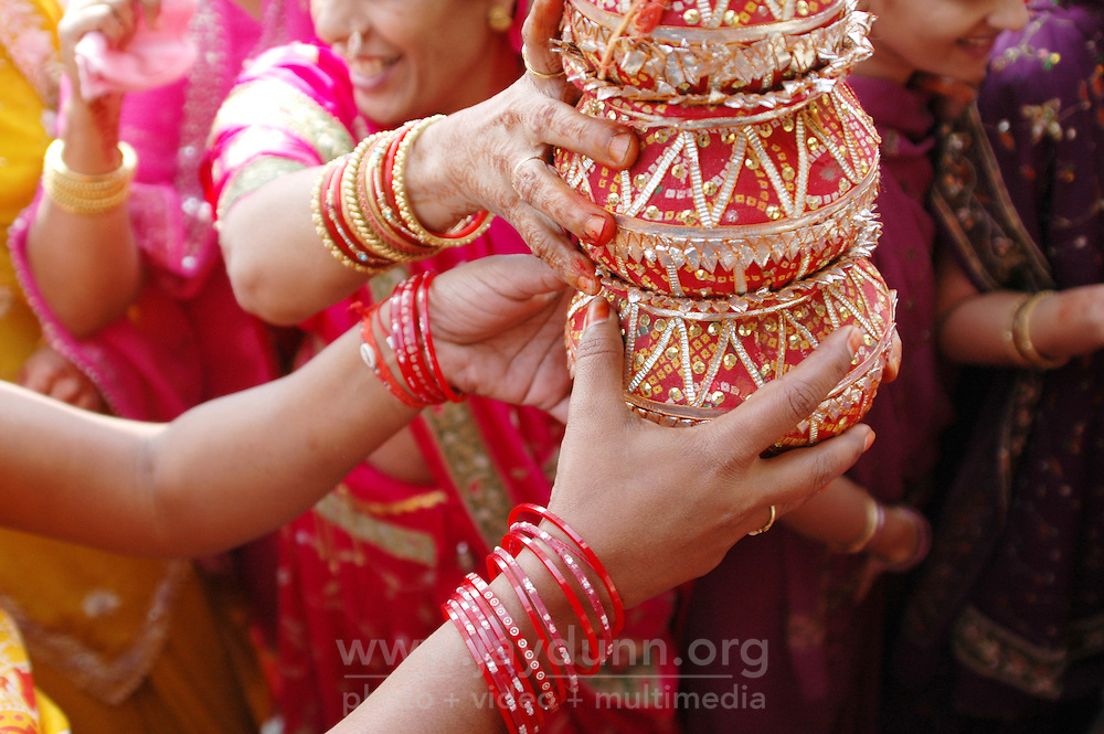 India, Maharashtra, Nasik, 2007. Wedding participants share the joy of their friend's wedding. Women will walk along the route with these jars on their heads.