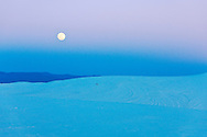 Full moon rising over the white sand dunes of White Sands National Monument, New Mexico