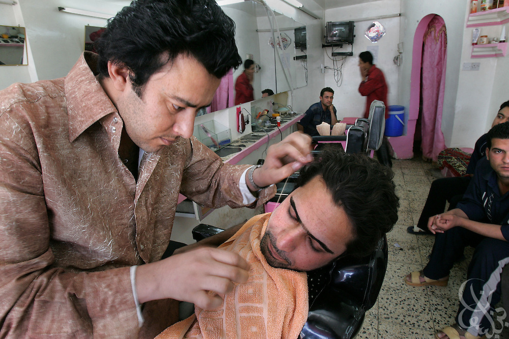 Iraqi barber Hussein Zamil removes facial hair with a piece of twine May 06, 2005 at the Shark barbershop in  Baghdad, Iraq.
