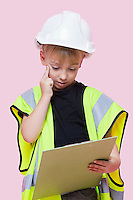 Portrait of a thoughtful young boy dressed as construction worker looking at clipboard over pink background